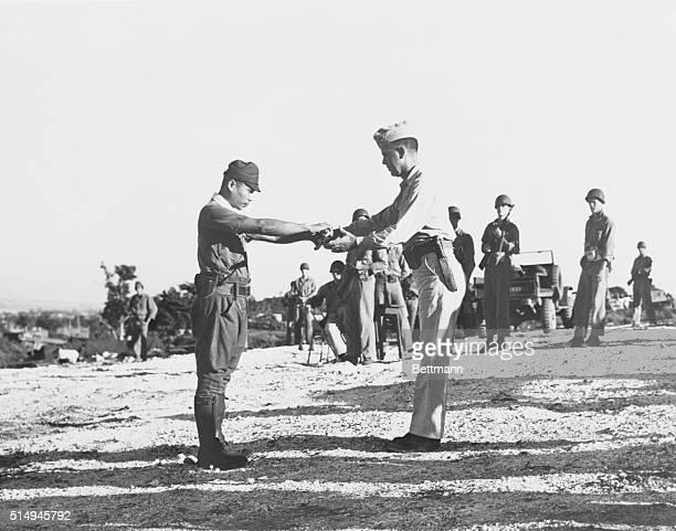 Japanese Imperial Army Capt. Sakae Oba surrenders his samurai sword to Lt. Col. Howard C. Kurgis, USMC, of Cawker City, Kan., on Saipan. Oba and 46...