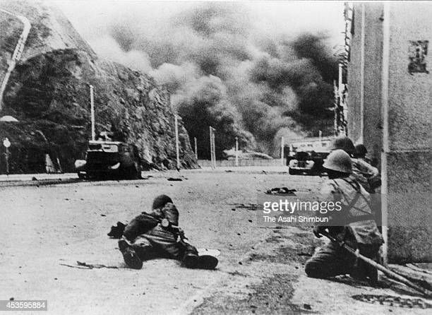 Japanese Imperial army soldiers approach to tanks of British Hong Kong during Battle of Hong Kong on December 21 1941 in Hong Kong