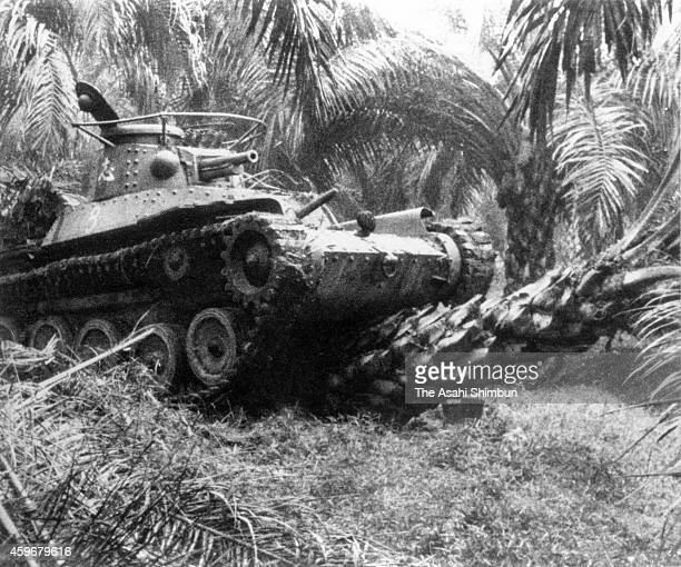 A Japanese Imperial Army tank proceeds with falling palm trees toward Singapore circa 1942 in Malaysia