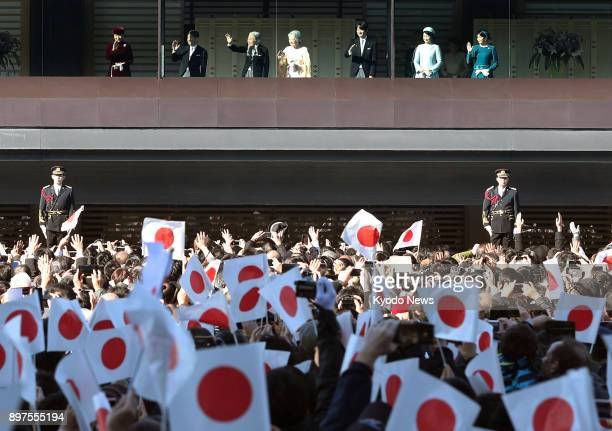 Japanese imperial family members wave to the crowd gathered to celebrate Emperor Akihito's 84th birthday at the Imperial Palace in Tokyo on Dec 23...