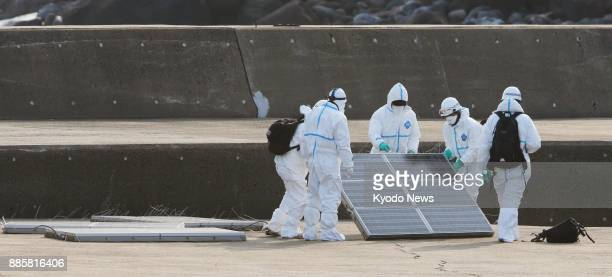 Japanese investigators hold a solar panel at the port of an uninhabited island off Matsumae Hokkaido on Dec 4 2017 Police the coast guard and a local...