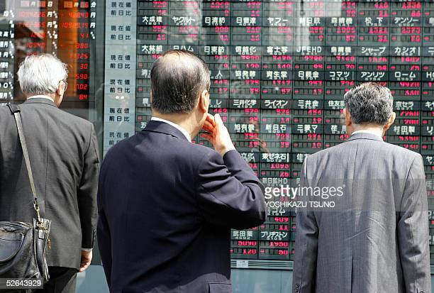 Japanese investors gaze at a share prices board anxiously in Tokyo as the share prices dropped sharply at the Tokyo Stock Exchange 18 April 2005...