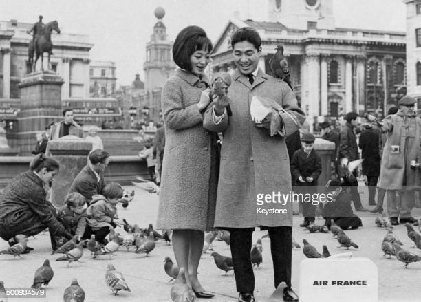 Japanese Kabuki actor Ichikawa Ennosuke III and his wife feed the pigeons in Trafalgar Square on a visit to London England 27th February 1965