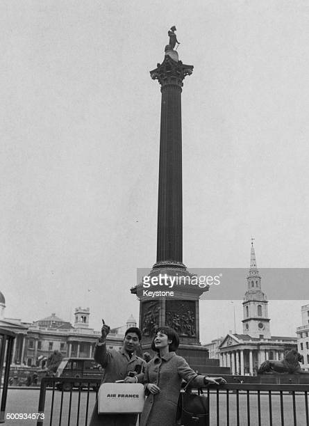 Japanese Kabuki actor Ichikawa Ennosuke III and his wife stand by Nelson's Column on a visit to London England 27th February 1965