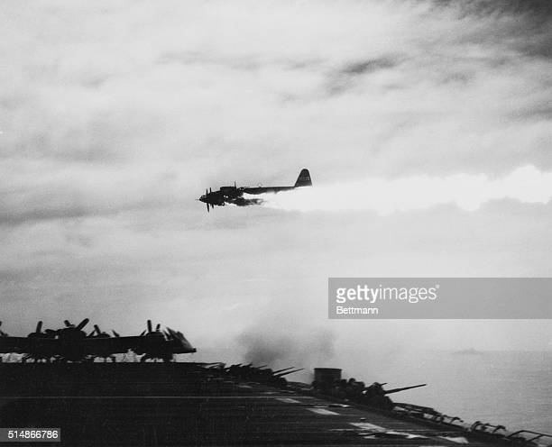 Japanese Kamikaze plane misses hitting a U.S. Aircraft carrier after being damaged by the carrier's guns.