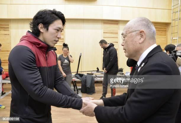 Japanese kayaker Seiji Komatsu receives encouragement from Japan Canoe Federation President Shoken Narita as they shake hands in Komatsu Ishikawa...
