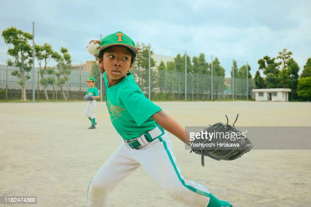 japanese kid (6-7) baseball player throwing ball on field - sporting term stock-fotos und bilder
