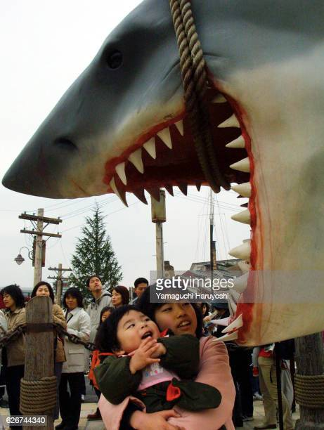 A Japanese kid seems impressed with the reproduction of Jaws during a press preview of Universal Studios Japan in Osaka The theme park's grand...