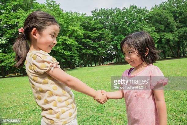Japanese kid shaking hands in a park