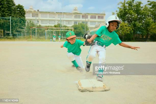 japanese kids baseball player running on field - base equipamento desportivo imagens e fotografias de stock