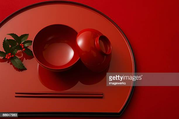 Japanese lacquer ware with chopsticks against red background, close-up