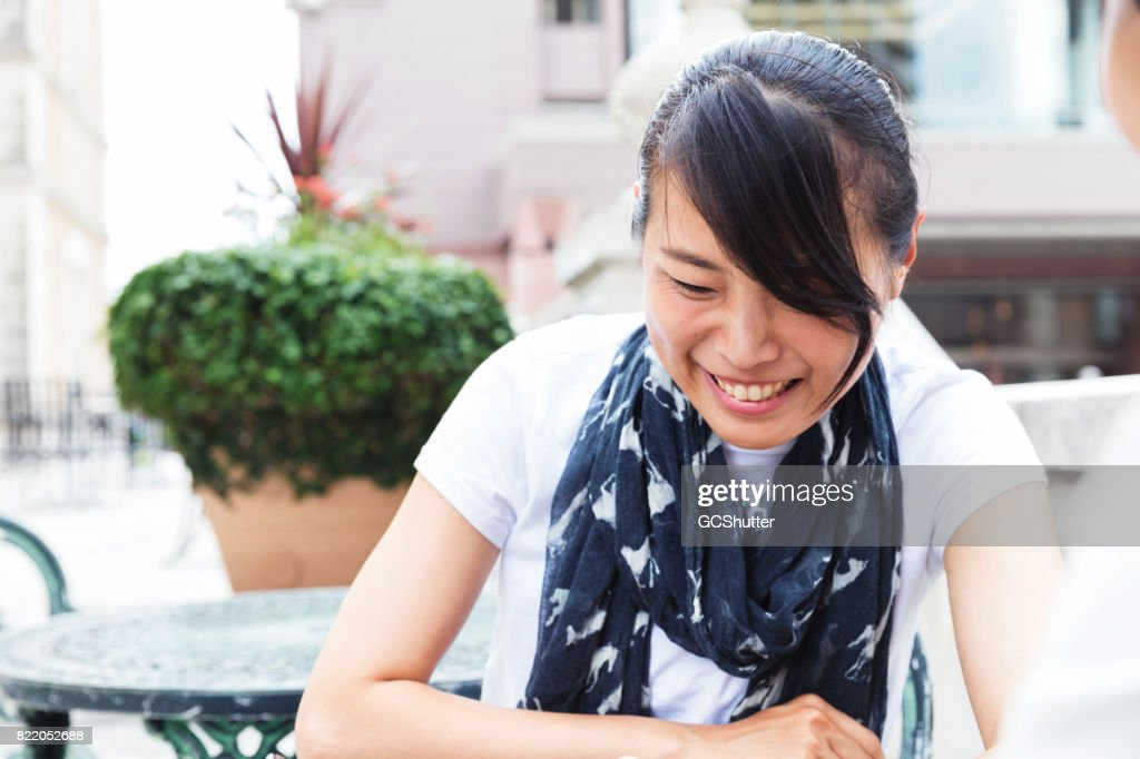 Japanese lady laughing at the topic of the conversation : Stock Photo