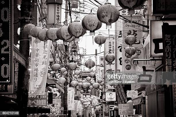 Japanese Lanterns Over Street Amidst Buildings