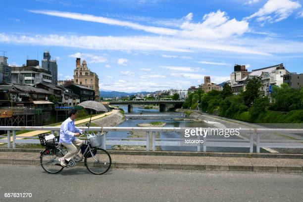 Japanese Lifestyle - A senior biker slowly biking through the Donguri-bashi Bridge (団栗橋) after shopping on a beautiful casual day in Kyoto (京都) Japan