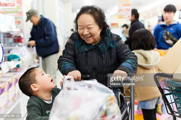 japanese little boy and his grandmother in supermarket - 欲望 ストックフォトと画像