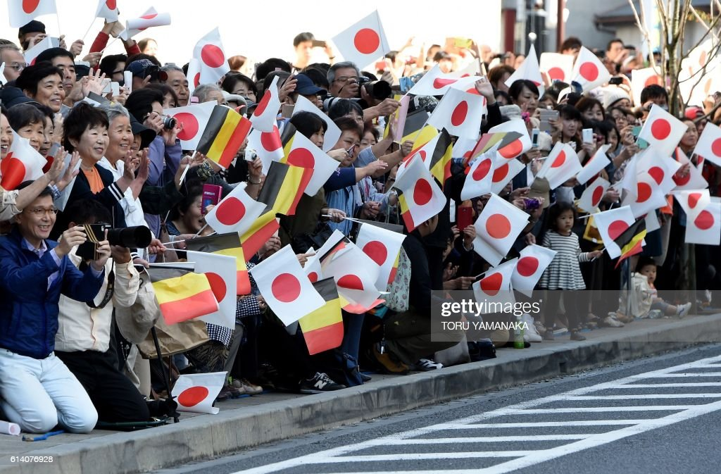 TOPSHOT - Japanese local residents wave Japanese and Belgian flags as Belgium's King Philippe and Empress Queen Mathilde, Japanese Emperor Akihito and Empress Michiko leave Oyama Station in Oyama for a local community center in Yuki on October 12, 2016. The Belgium's King Philippe and Queen Mathilde are on a six-day state visit to Japan. / AFP / POOL / TORU