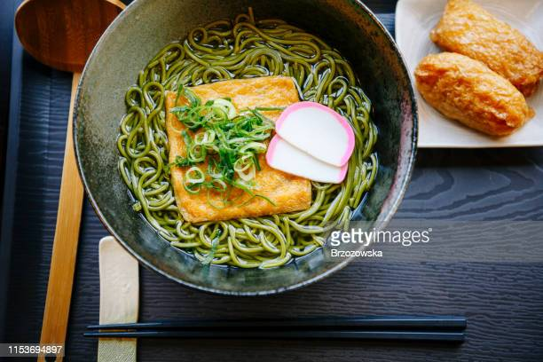 japanese lunch set: green soba noodle soup with tofu and inarizushi. - soba stock pictures, royalty-free photos & images
