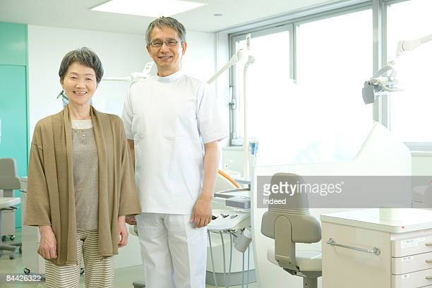Japanese male dentist and senior woman smiling