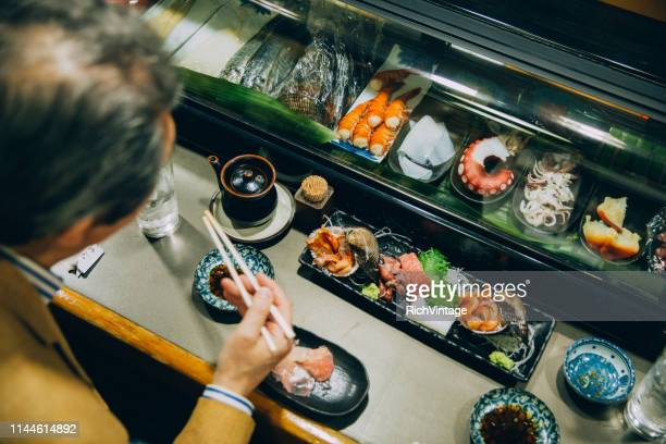 japanese male eating sushi - sushi restaurant stock photos and pictures