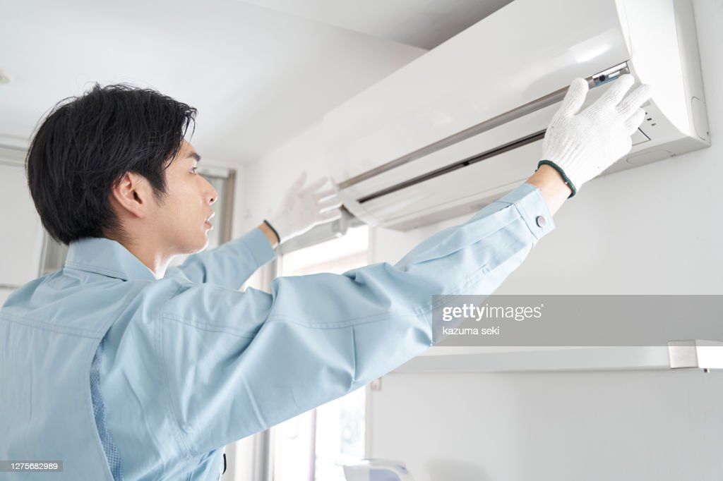 Japanese male electrical contractor checking for air conditioners for home use : Stock Photo