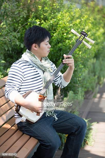japanese male playing the shamisen - vangen imagens e fotografias de stock