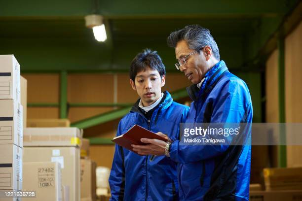 japanese male workers in a warehouse - オーバーオール ストックフォトと画像