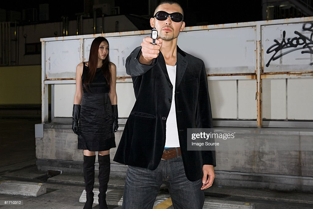 Japanese man aiming gun at camera : Stock Photo