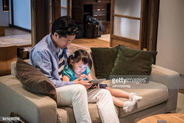 日本男と娘を一緒にタブレットを使用してソファの上に座って