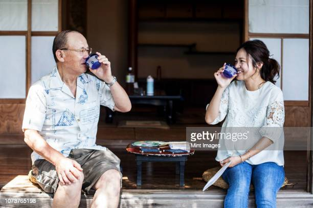 japanese man and woman sitting on floor on porch of traditional japanese house, drinking tea. - 温かいお茶 ストックフォトと画像