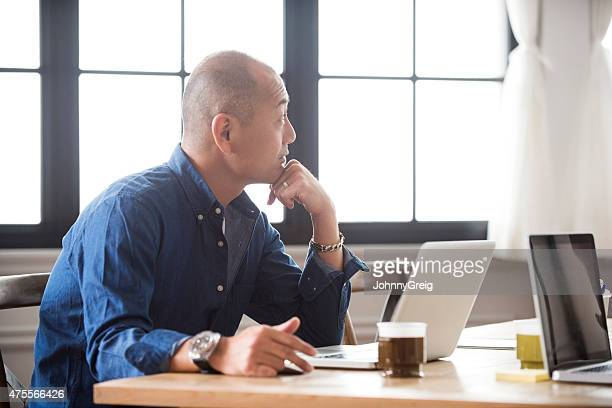 Japanese man at work on laptop computer