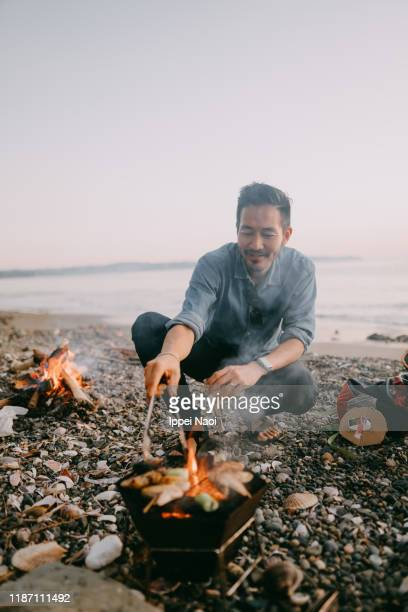 japanese man barbecuing at beach camping site, tokyo bay - キャンプ 1人 ストックフォトと画像