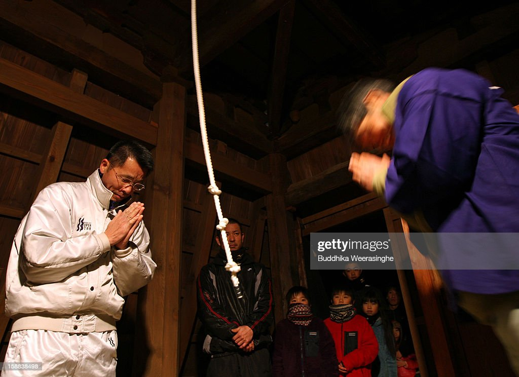 A Japanese man bows his head after ringing the bell at the Sagami-ji Buddhist temple on January 1, 2013 in Kasai, Japan. Japanese people attend the Buddhist temple at midnight on December 31 for the ringing of the temple bell to welcome in the New Year or 'Omisoka' as it is known in Japan. In Japanese belief there are 108 elements to the human mind, so the bell is rung 108 times as a blessing of happiness for the New Year.
