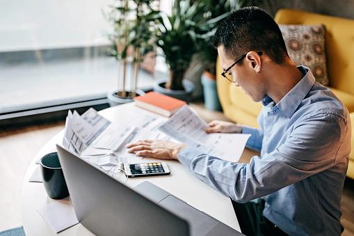 Japanese man calculating financial bills at home 1168618923