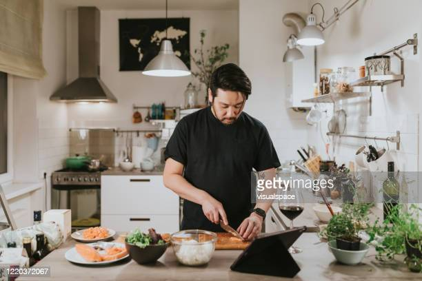 japanese man cuts fresh salmon while looking at digital tablet - cooking stock pictures, royalty-free photos & images