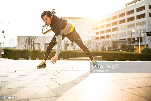 Japanese man doing stretching on the city