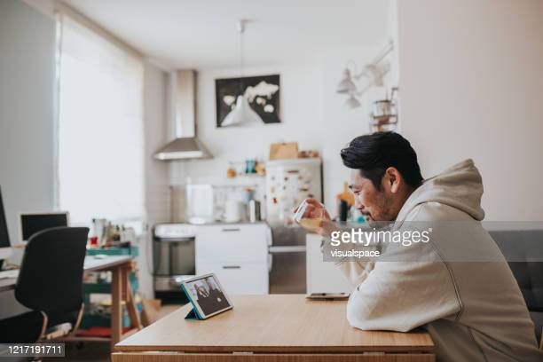Japanese man drinking whiskey with friends in online meeting during social distancing times