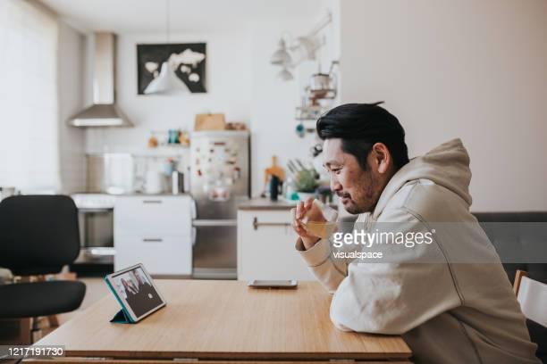社会的な時間の間にオンライン会議で友人とウイスキーを飲む日本人男性 - 飲む ストックフォトと画像