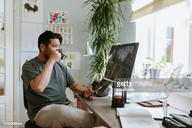 japanese man drinks morning coffee while using smart phone - east asian ethnicity stock pictures, royalty-free photos & images