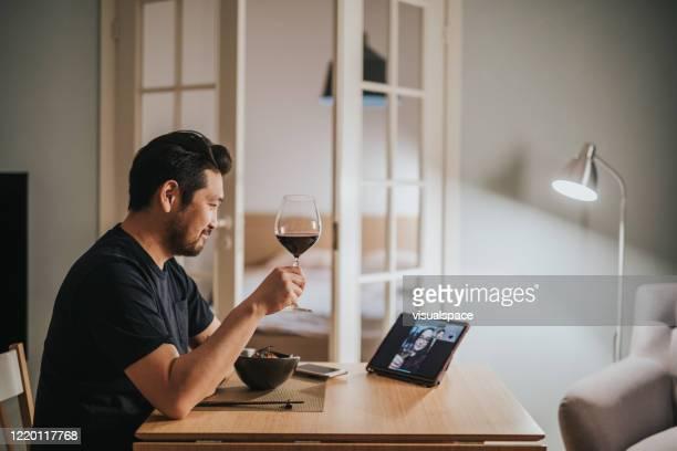 日本の男は、ビデオコール仮想ディナーの上に彼のガールフレンドとワインを飲みます - evening meal ストックフォトと画像