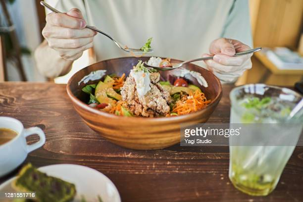 japanese man eating a vegan lunch at a vegan cafe - vegetarian food stock pictures, royalty-free photos & images