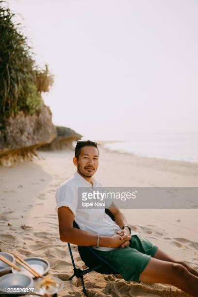 japanese man enjoying beach campsite at sunset - キャンプ 1人 ストックフォトと画像
