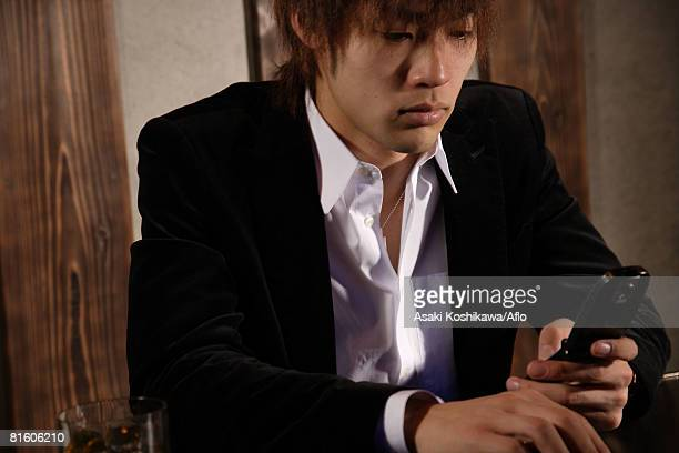 Japanese man holding cellphone with a cigarette at the same time