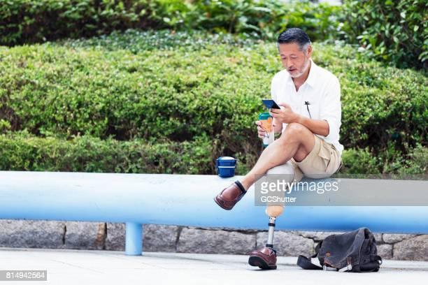 Japanse man bezit zijn koffie zoals hij gebruikt een instant messaging-toepassing op zijn telefoon