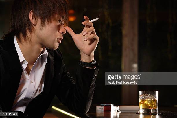 Japanese Man in bar thinking w/ cigarette and scotch-whiskey