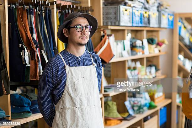 a japanese man in his 30's stands in his shop. - 後ろ手 ストックフォトと画像