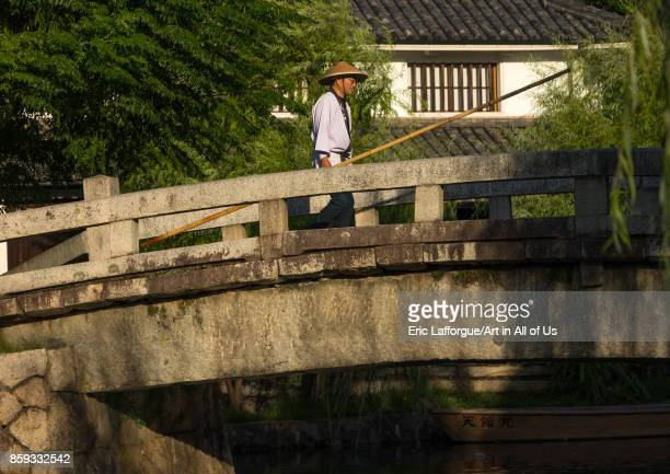 Japanese man in traditional clothing crossing a bridge Okayama Prefecture Kurashiki Japan on August 25 2017 in Kurashiki Japan