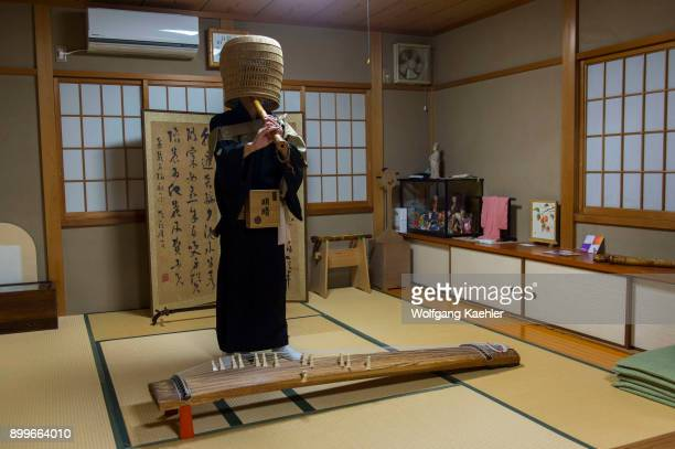 Japanese man in traditional monks outfit in Kyoto Japan is playing a traditional Japanese shakuhachi a Japanese endblown flute