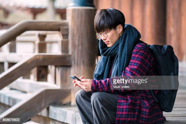 japanese man is using a phone at hyakumanben chionji temple - tdub_video stock pictures, royalty-free photos & images