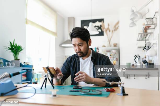 japanese man learns how to repair his smart hone - tutorial stock pictures, royalty-free photos & images