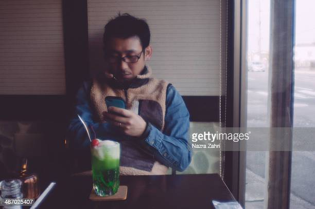 Japanese man looking at smartphone in a cafe